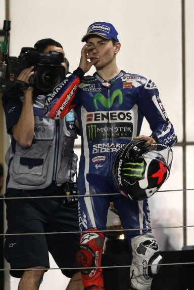 Spanish rider Jorge Lorenzo of Movistar Yamaha MotoGP celebrates on the podium on March 20, 2016 after winning the Qatar Grand Prix at the Losail International Circuit in the capital Doha. / AFP / KARIM JAAFAR
