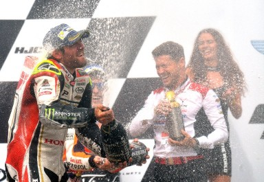 Winner Moto GP rider Cal Crutchlow of Great Britain celebrates on the podium with champagne after the MotoGP competition of Grand Prix of Czech Republic at Masaryk Circuit on August 21, 2016 in Brno, Czech Republic. / AFP PHOTO / Michal Cizek